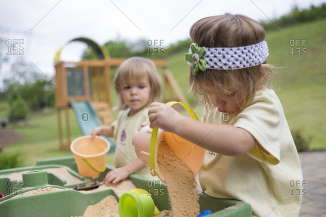 Twin girls playing in a sandbox