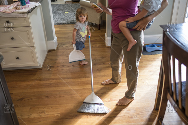 Twin toddlers helping with housework