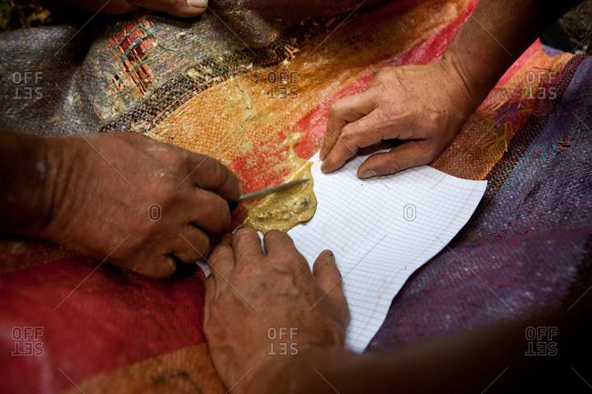 Hands mixing fresh coca paste