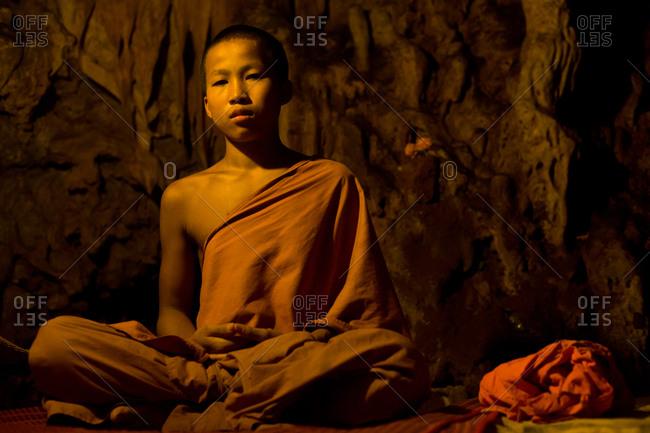 Luang Prabang, Laos - November 1, 2009: Young buddhist monk in cave
