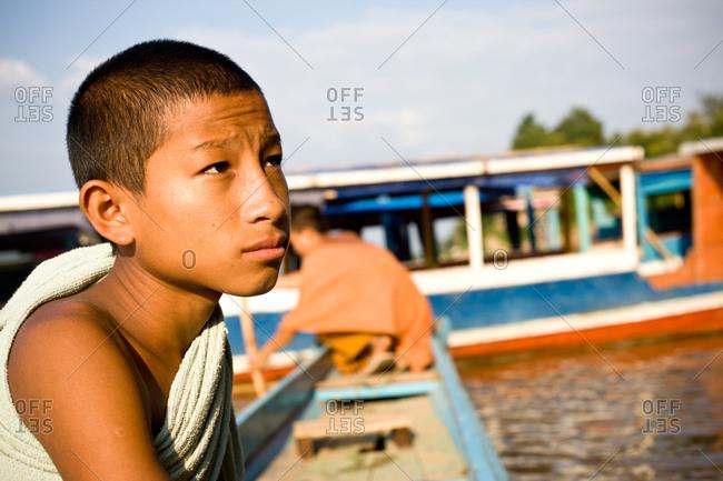 Luang Prabang, Laos - November 1, 2009: Buddhist boy on boat