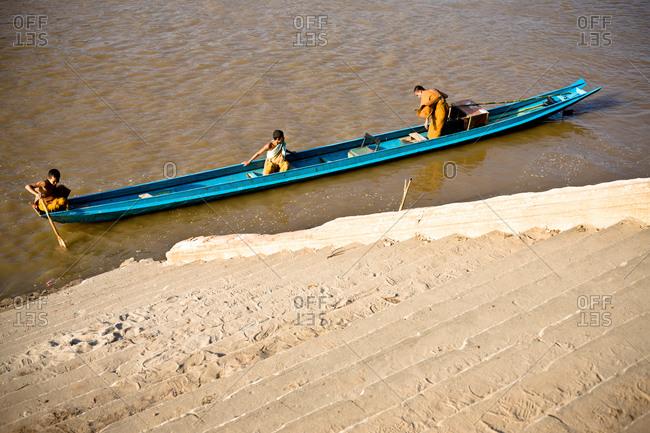 Luang Prabang, Laos - November 1, 2009: Buddhist boys rowing in boat