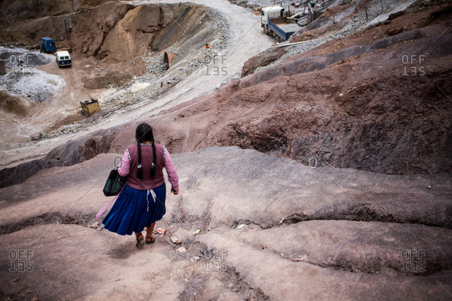 A bolivian woman walks down the side of a mining hill