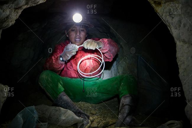 A Potsi, Bolivia - February 8, 2010: Child miner manipulates dynamite