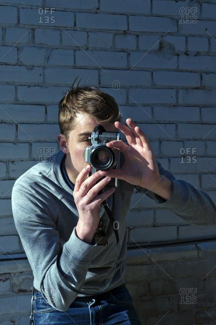 Young man adjusting camera lens