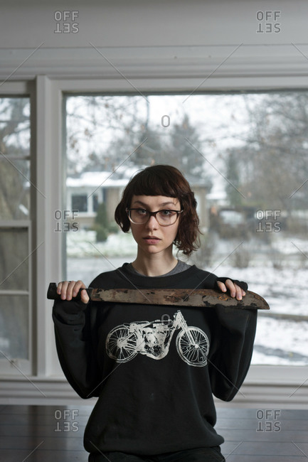 Young woman holding a rusty machete with piercing gaze