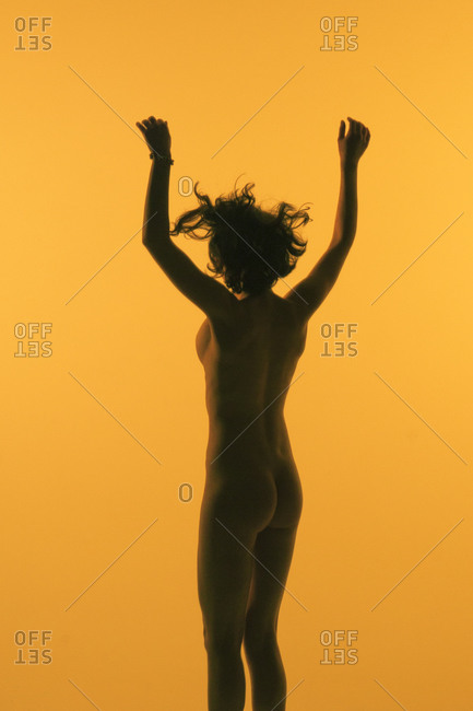 Female dancer jumping against yellow-orange background
