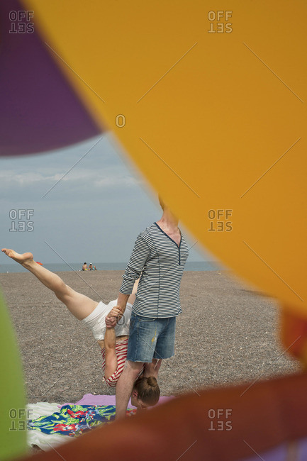 Couple practicing gymnastics on a beach