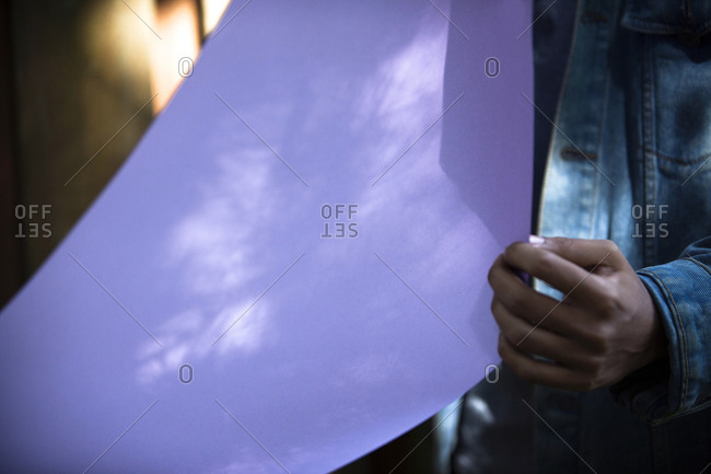 Mid section view of a woman folding a purple paper