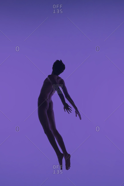 Male dancer leaping against purple background