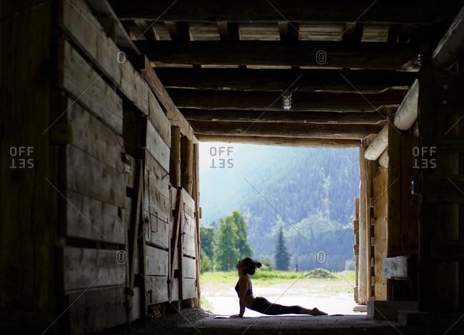 Woman doing yoga pose in barn