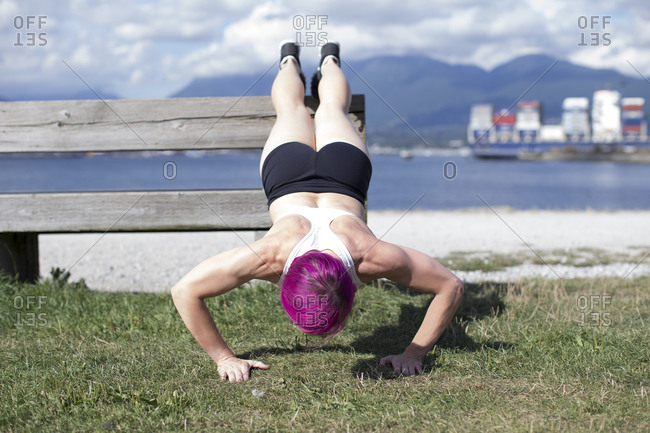 Woman doing push-ups in waterside park, Vancouver