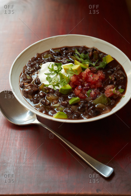Black bean soup with sour cream, tomatoes and avocado