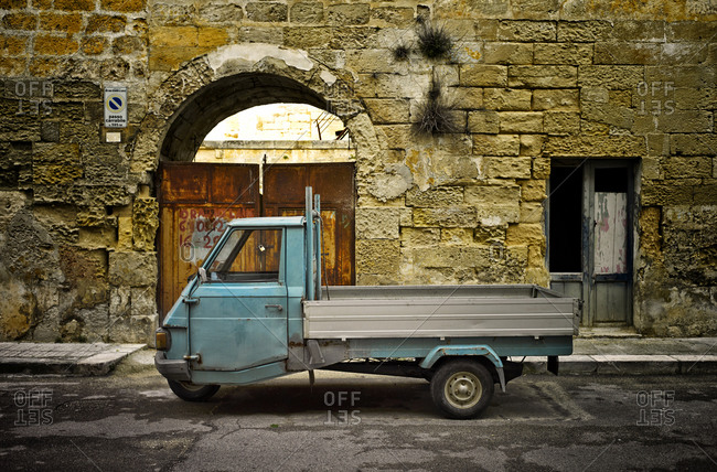 Parking Piaggio Ape in front of house facade