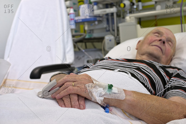 Senior man with cannulae and bandage being in intensive care after heart attack