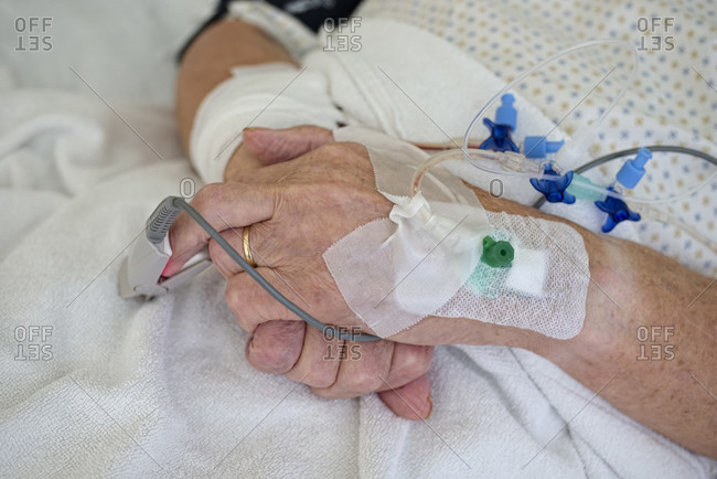 Hands of senior man with cannulae and bandage being in intensive care