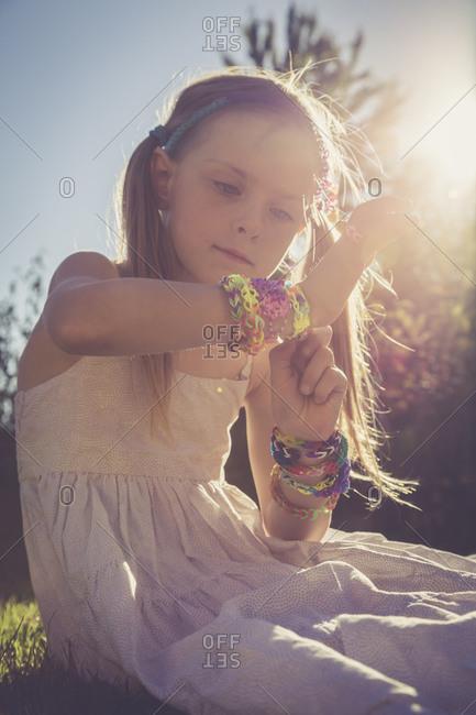 Portrait of little girl sitting at sunlight wearing plenty of loom bracelets