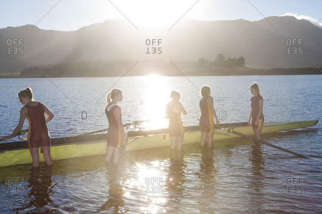 Five female rowers in water