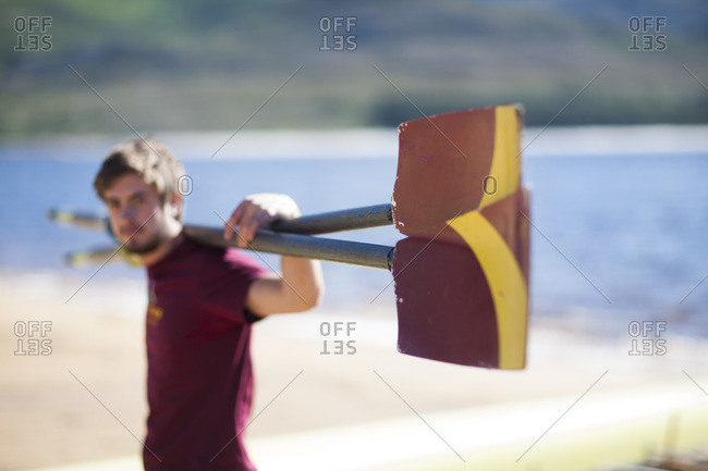Male rower holding oar at lakeshore