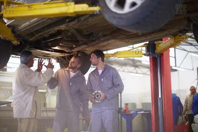 Two car mechanics with client in repair garage