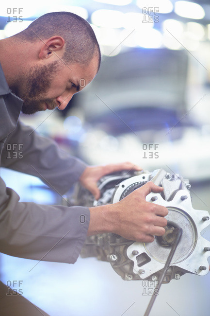 Car mechanic working on gearbox in repair garage