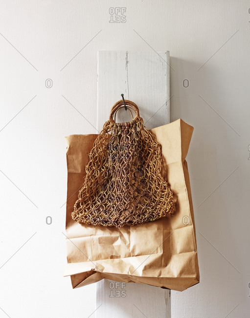 A paper and a woven bag on a peg