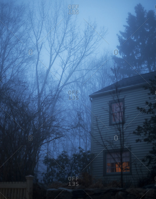 House shrouded in fog at dusk