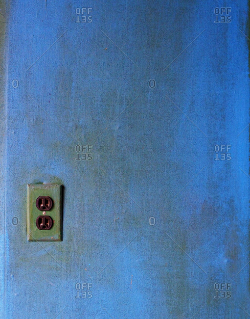 Old socket on a blue wall
