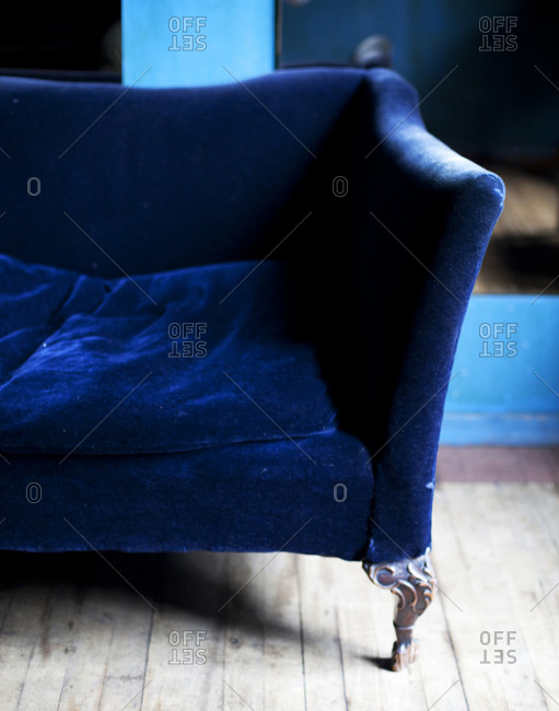 Blue velvet couch with a claw foot leg