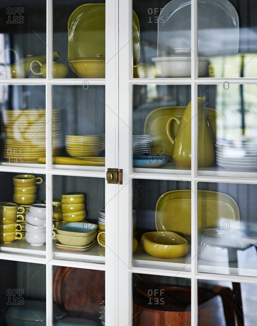 Stacked ceramic dishware in a kitchen cabinet