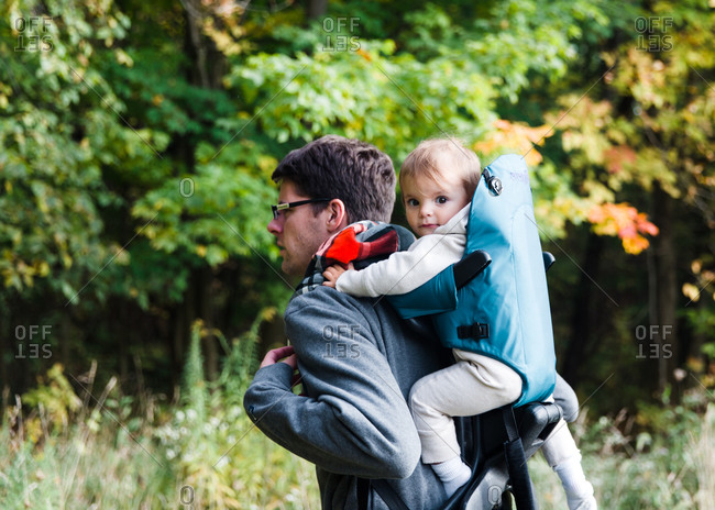 Father carrying daughter in backpack