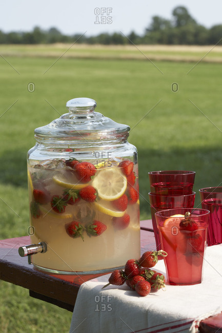 Lemonade with strawberries in glass dispenser outside