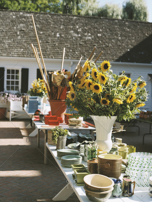 Various kitchenware and flowers at outdoor estate sale