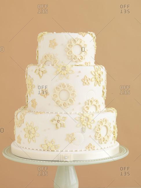 Three tier wedding cake on pink background