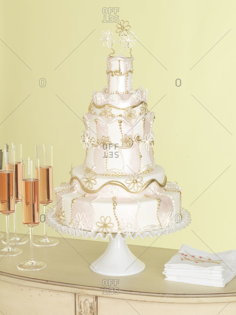 Ornate wedding cake and champagne glasses on cabinet