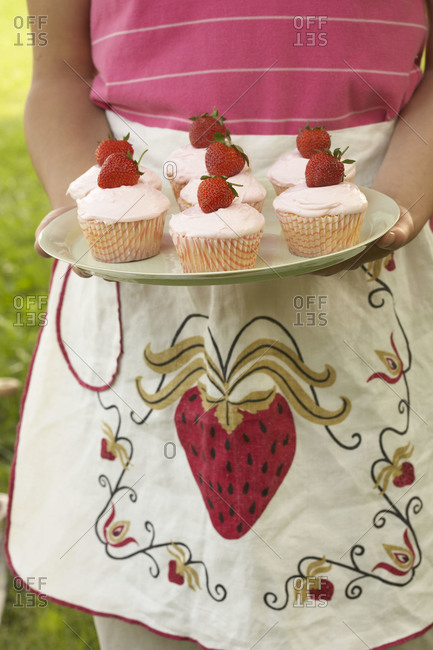 Girl in apron carrying strawberry cupcakes