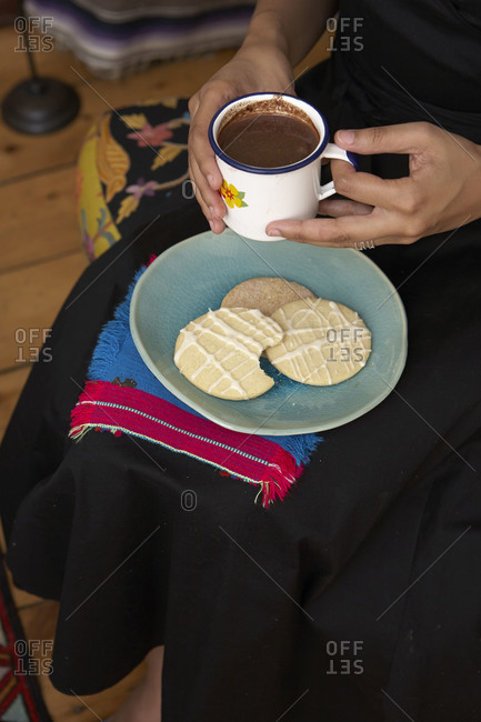 Woman sitting with cookies and hot cocoa