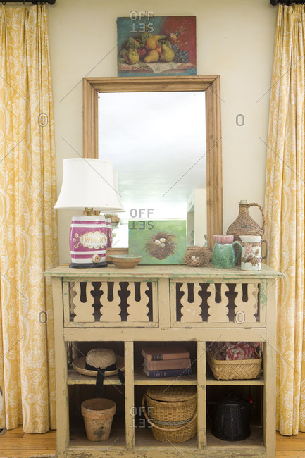 A side cabinet with various decor and mirror