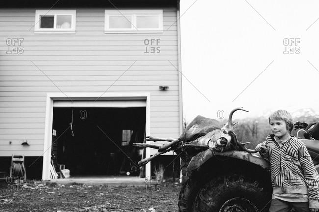 A boy stands next to an ATV and dead deer