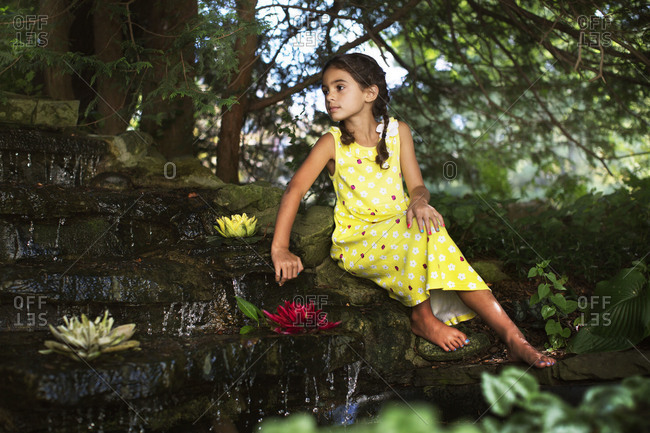 Girl sitting by a landscaped waterfall