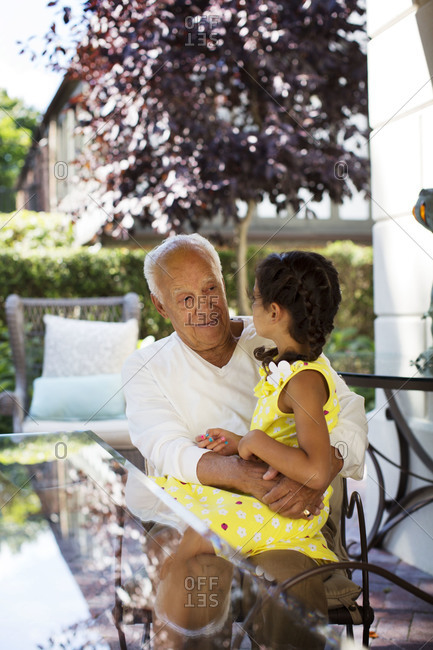 Grandfather and granddaughter sitting  on patio