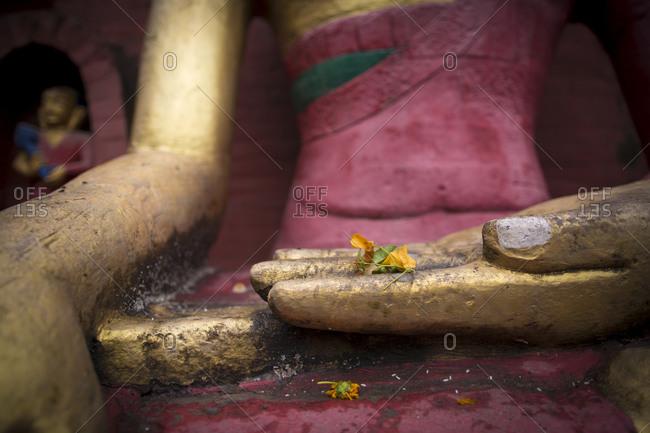 A statue of the Buddha holds yellow flowers at Swayabu Temple in Kathmandu, Nepal