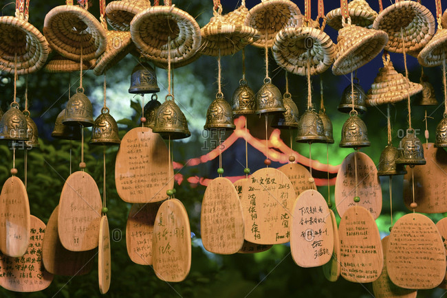 Lucky charms in form of small bells, wicker hats and wooden plates with Chinese hand writing at Shenyuan in Shaoxing