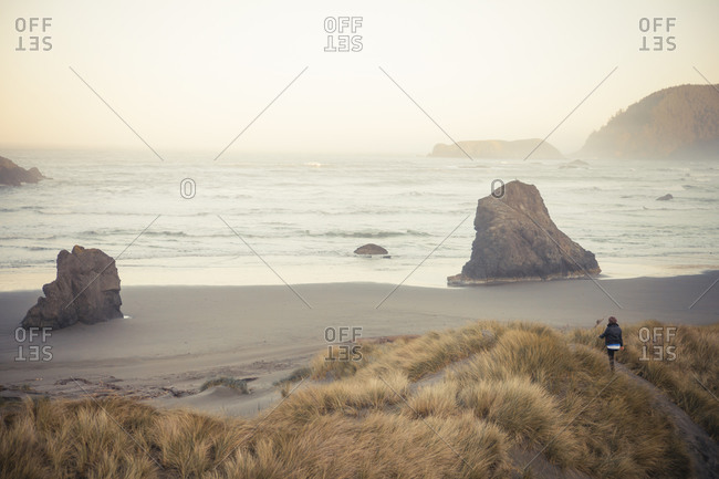 A young woman approaches the beach along the Oregon Coast at Meyers Creek Beach, Pistol River State Park