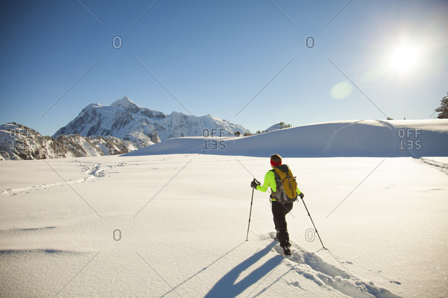 A female snowshoer crosses a large snowfield with Mount Shuksan in the background