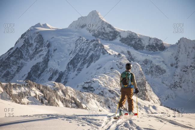 A skier crosses a snowfield with Mount Shuksan in the background during a winter ski tour