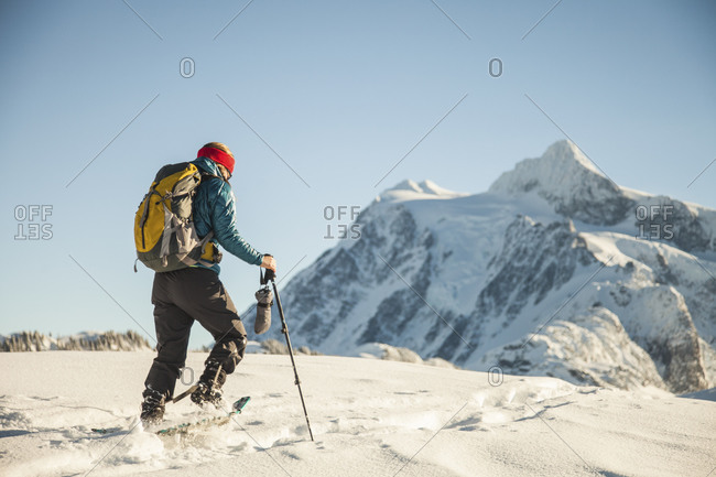 A female snowshoer crosses a snowfield with Mount Shuksan in the background