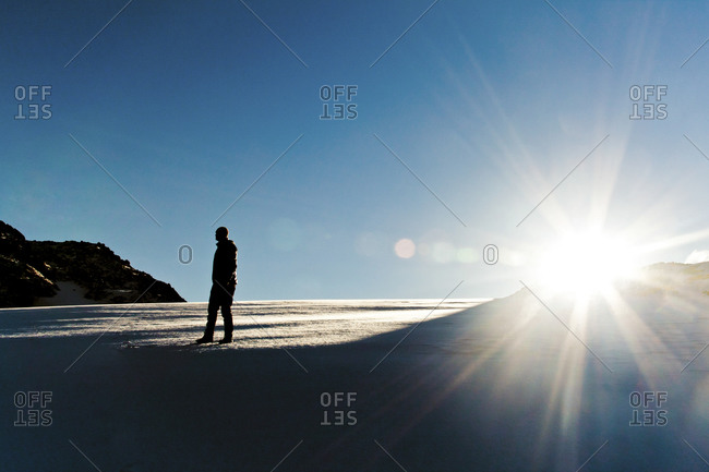 A climber enjoys the sunrise from a snowfield in the alpine near Chilliwack, BC, Canada
