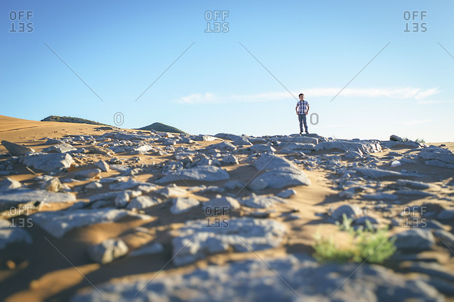 A boy stands in the desert