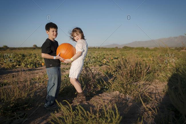 A girl and boy support a heavy pumpkin